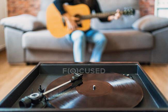Анонимная женщина, играющая на гитаре, сидит дома на диване и учится с помощью онлайн-уроков рядом с проигрывателем. — стоковое фото