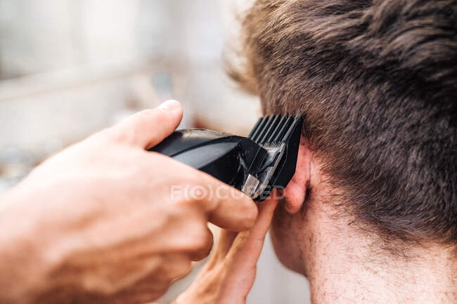 Male with hair trimmer cutting hair of guy in contemporary bathroom at home — Stock Photo