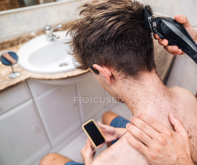 Desde arriba vista posterior de cultivo sin camisa masculina se centra en la pantalla y ver video tutorial después de auto corte de pelo en el baño de luz en el hogar como concepto malas decisiones o resultado de auto aislamiento - foto de stock