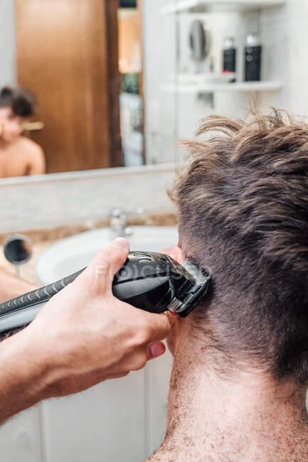 Maschio con tagliacapelli taglio capelli di ragazzo in bagno contemporaneo a casa — Foto stock