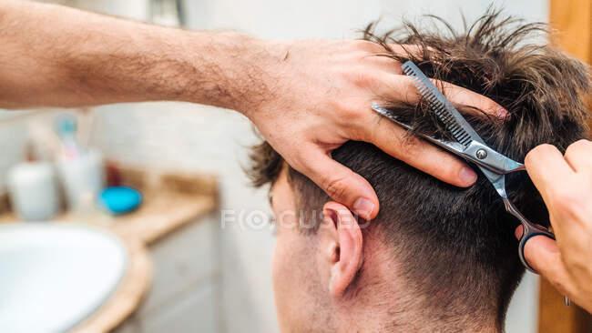 Vista posteriore di maschio irriconoscibile facendo taglio di capelli al ragazzo utilizzando forbici contro l'interno sfocato del bagno leggero a casa — Foto stock