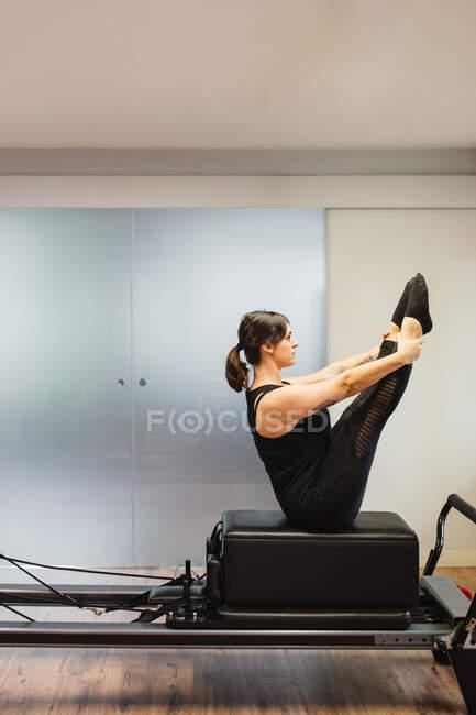 Vista lateral de una mujer fuerte en ropa deportiva haciendo ejercicios abdominales mientras se equilibra en la máquina de pilates durante el entrenamiento - foto de stock