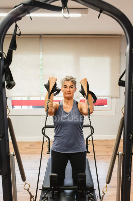 Определенная женщина в спортивной одежде накачивает мышцы полосами сопротивления при использовании пилатеса и смотрит в камеру во время тренировки — стоковое фото