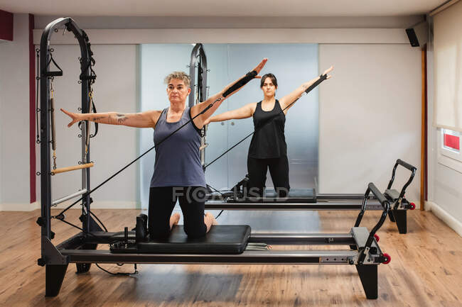 Женщины в спортивной одежде делают упражнения на тренажерах пилатеса и пилатеса с использованием оборудования для сопротивления металлу — стоковое фото
