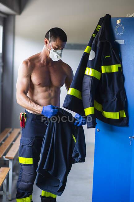 Bombero serio con el torso desnudo y en guantes de látex de pie con mascarilla respiradora cerca del armario en la estación de bomberos mientras se prepara para el trabajo - foto de stock