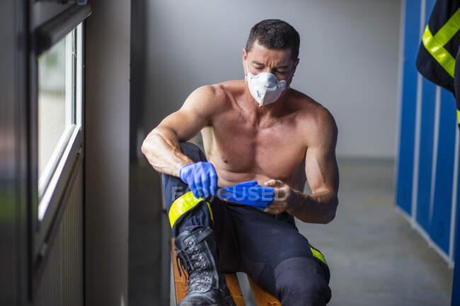 Bombero serio con torso muscular sentado en un banco de madera en la estación de bomberos y quitándose guantes de látex - foto de stock