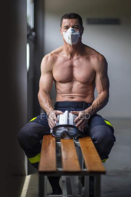 Fuerte bombero macho maduro con torso desnudo sentado en el banco con máscara y sosteniendo un casco mientras mira la cámara - foto de stock