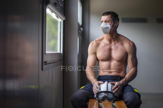 Fuerte bombero macho maduro con torso desnudo sentado en el banco con máscara y sosteniendo un casco mientras mira hacia otro lado - foto de stock