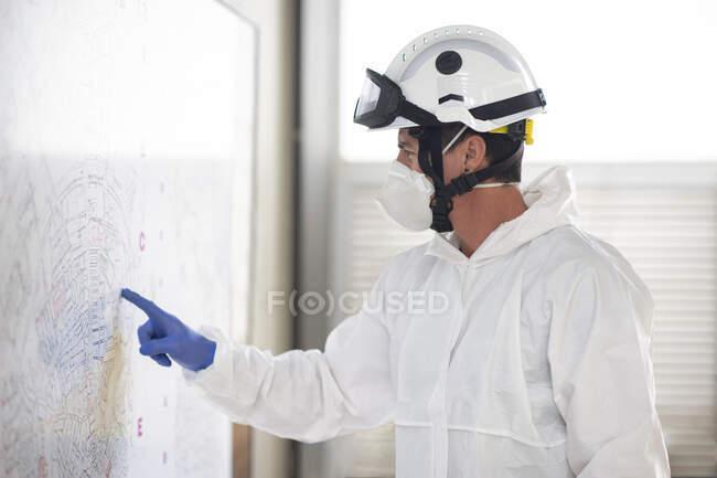 Seitenansicht eines Feuerwehrmannes in Schutzkleidung und Atemschutzmaske, der am Feuerwehrhaus steht und auf eine an der Wand befestigte Papierkarte zeigt — Stockfoto