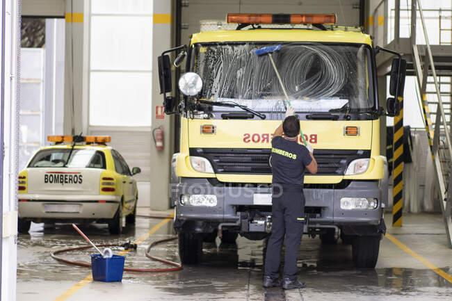 Пожарный в форме стоит у пожарной станции и чистит лобовое стекло автомобиля — стоковое фото