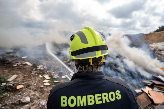 Back view of brave fireman in protective uniform standing with hose and extinguishing fire on dump in mountains — Stock Photo