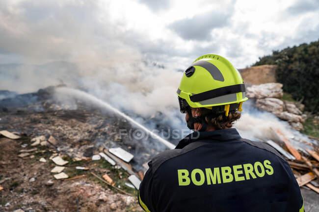 Обратный вид отважного пожарного в защитной форме, стоящего со шлангом и тушащего пожар на свалке в горах — стоковое фото