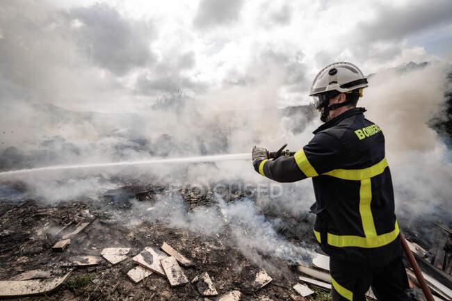 Вид сбоку на храброго пожарного в защитной форме, стоящего со шлангом и тушащего пожар на свалке в горах — стоковое фото
