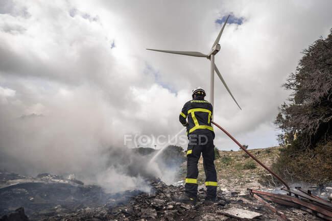 Vista trasera de valiente bombero en uniforme de protección de pie con manguera y fuego de extinción en el vertedero en las montañas - foto de stock