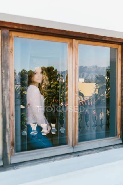Поперечний вигляд спокійної жінки в повсякденному одязі, яка дивиться на камеру і відпочиває біля затіненого вікна з відображенням тропічних дерев. — стокове фото
