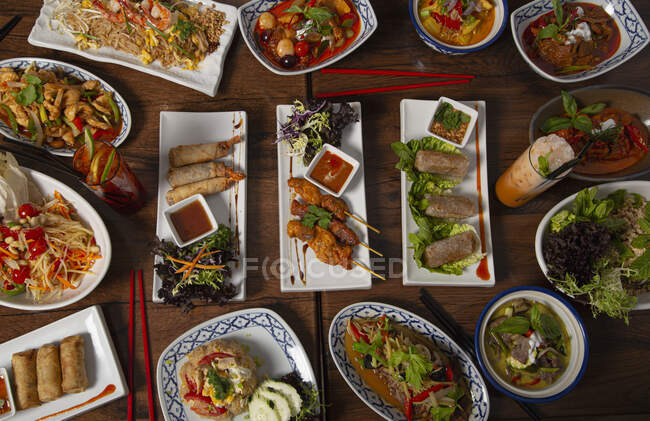 Top view of spicy Thai food served on wooden table with chopsticks — Stock Photo