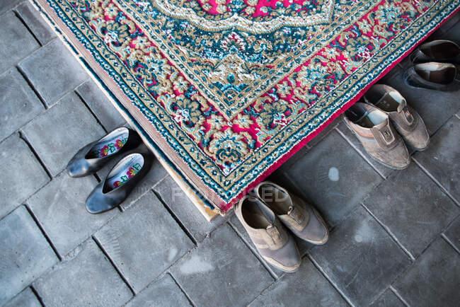 Барвистий килим і старе взуття на кам'яній підлозі в мусульманській церкві. — стокове фото