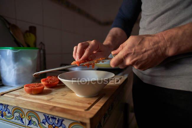 Détail des mains d'un homme grille tomate sur le dessus d'un morceau de bois dans une cuisine — Photo de stock