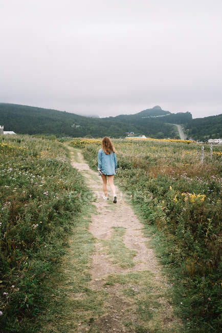 Unrecognizable female in summer wear walking along sandy pathway between meadows with flowers on overcast day — Stock Photo