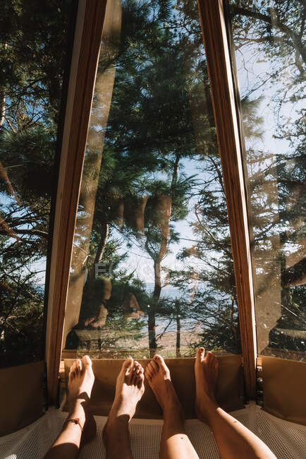 Feet of boyfriend and girlfriend lying together in hammock in camp house and admiring view of wood through window — Stock Photo