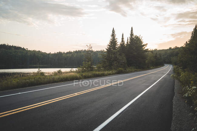 Asphalt road going near peaceful lake and green forest against cloudy sunset sky in La Mauricie National Park in Quebec, Canada — Stock Photo