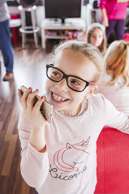 From above delighted girl in glasses smiling and looking away while recording audio message on smartphone at home — Stock Photo