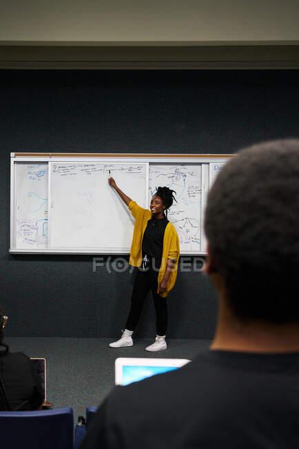 Femme afro-américaine pleine longueur en vêtements décontractés pointant vers le tableau blanc et expliquant les données au public pendant la conférence à l'université — Photo de stock