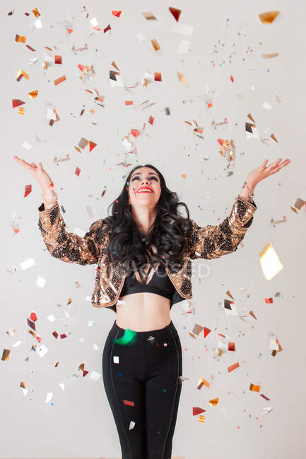 Slim donna in abito elegante sorridente e guardando verso l'alto mentre si cerca di catturare coriandoli d'oro durante la festa contro sfondo grigio — Foto stock