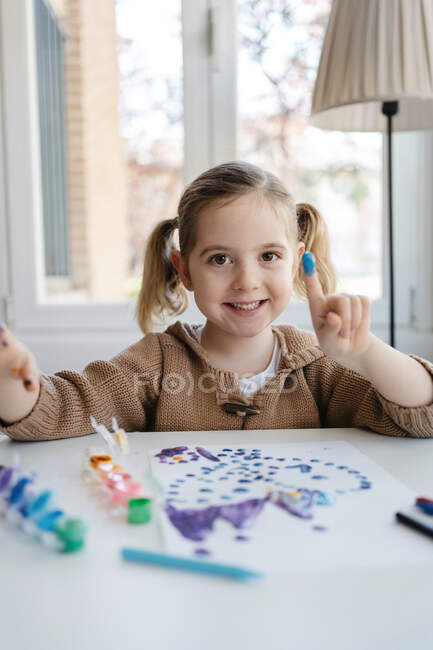 Menina pré-escolar bonito em roupas casuais sentado à mesa e apontando o dedo com tinta para a câmera enquanto pintura quadro abstrato — Fotografia de Stock