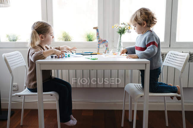 Side view of little blond kids in casual wear drawing with colorful gouache while spending time together at light living room — Stock Photo