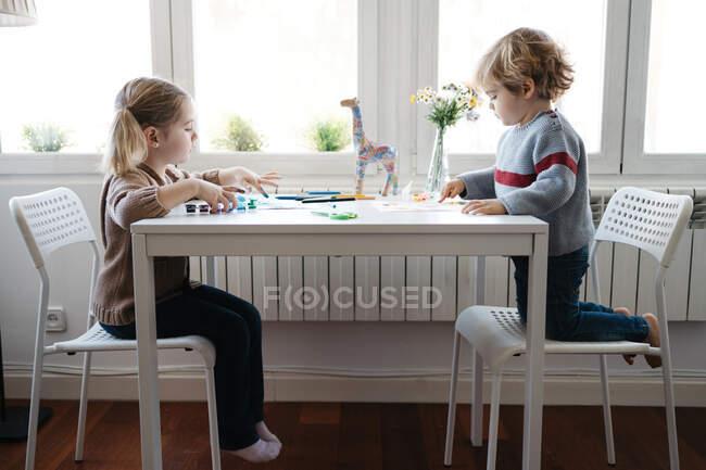 Vista lateral de los niños rubios en el dibujo de ropa casual con gouache colorido mientras pasan tiempo juntos en la sala de estar ligera - foto de stock