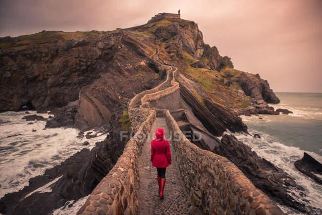 Vista posteriore di turista donna irriconoscibile in abiti caldi a piedi verso ponte cappella durante il viaggio sull'isola di San Juan de Gaztelugatxe in Spagna — Foto stock