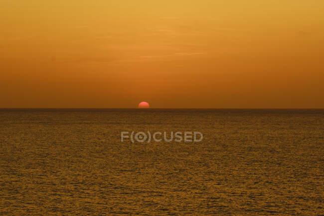 Amazing golden sunset over dark ocean — Stock Photo