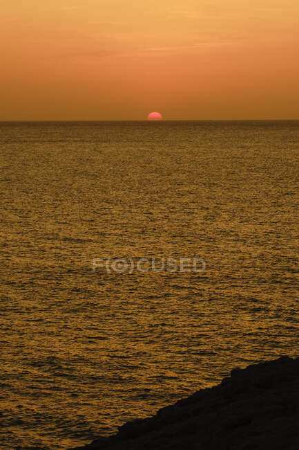 Amazing golden sunset over dark ocean — Stock Photo