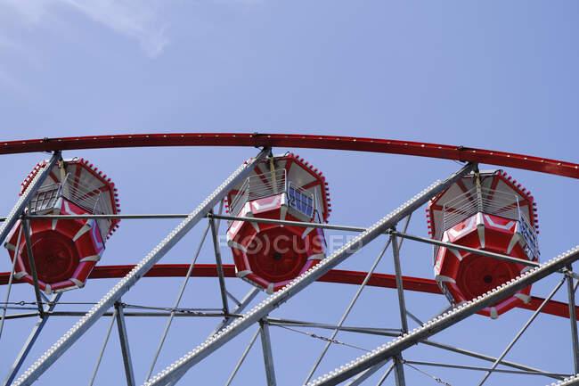 Знизу колеса Ферріса з червоними кабінами, розташованими на розважальному парку в сонячний день з синім небом. — стокове фото