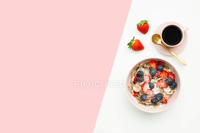 Top view of breakfast bowl with yummy muesli and berries placed on table with cup of coffee and fresh strawberries — Stock Photo