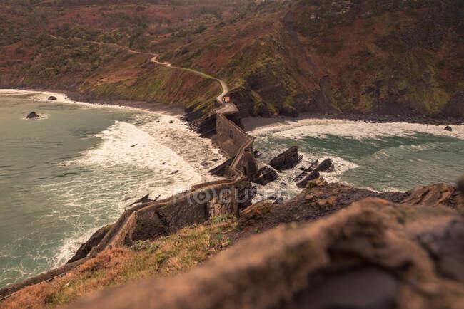 Dall'alto pittoresco paesaggio dell'isola Gaztelugatxe con lungo ponte di pietra che passa attraverso la riva del mare durante la giornata ventosa — Foto stock