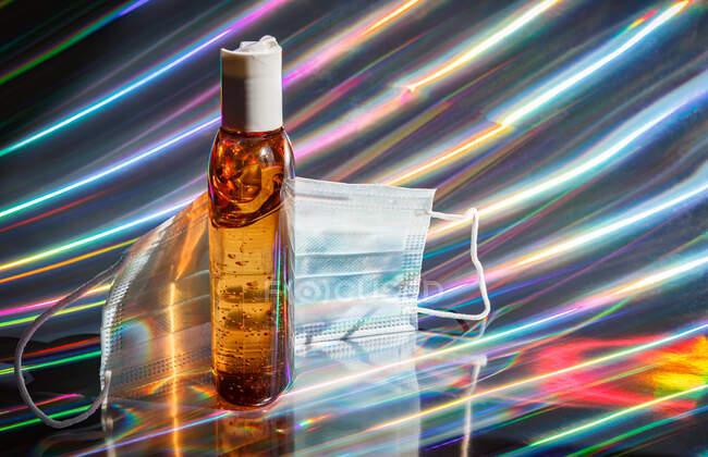 Mascarilla médica protectora y botella de gel desinfectante marrón sobre fondo holográfico brillante - foto de stock