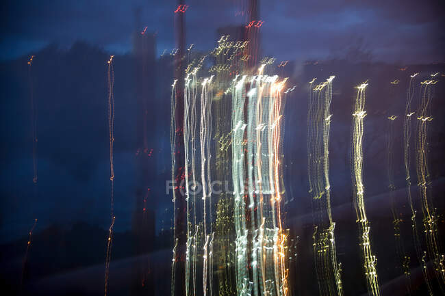 Blurred night white yellow lights of brightly lighting area of city with industrial pipes at dusk on cloudy evening — Stock Photo