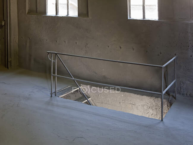 Interior of hallway with metal railings and staircase leading to exit of industrial building on sunny day — стокове фото