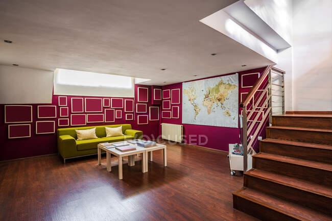 Современная просторная гостиная с деревянным полом и лестницей, обставленная ярко-зеленым диваном и украшенная геометрическими элементами на красных стенах — стоковое фото