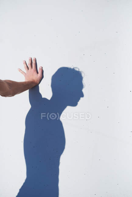 Side view of crop anonymous male standing and leaning palm on white wall with dark self shadow on sunny day — Stock Photo