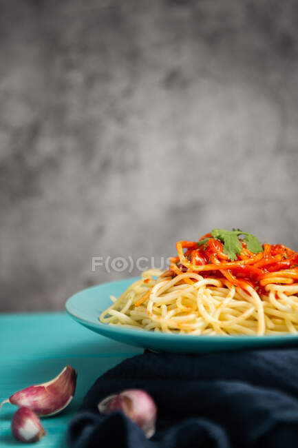 Голубая керамическая тарелка с макаронами и томатным соусом, украшенная петрушкой и базиликом, подается между зубчиком чеснока и парой помидоров на светло-голубом фоне — стоковое фото