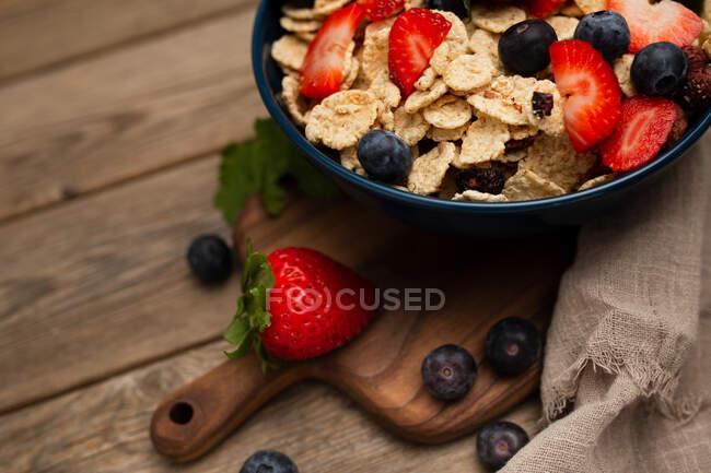 Desde arriba delicioso plato de desayuno de hojuelas de maíz con fresas y arándanos colocados en la tabla de cortar y decorado con tela de lino y bayas alrededor del plato sobre fondo de madera - foto de stock