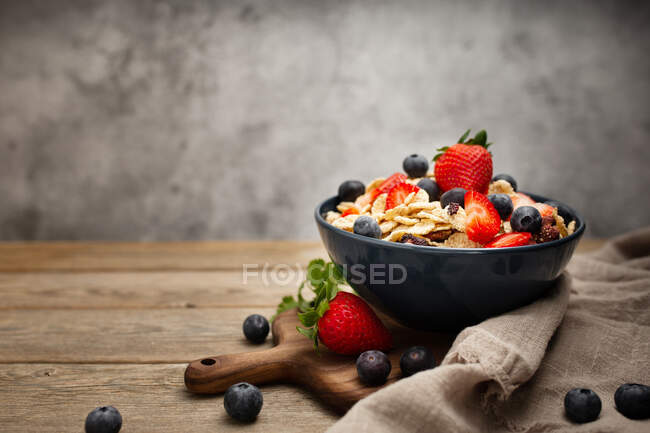 From above delicious breakfast bowl of corn flakes with strawberries and blueberries placed on cutting board and decorated with linen cloth and berries around dish on wooden table with gray background — Stock Photo