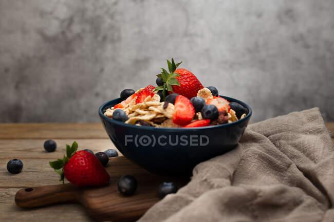 De cima deliciosa tigela de café da manhã de flocos de milho com morangos e mirtilos colocados na tábua de corte e decorados com pano de linho e bagas em torno do prato na mesa de madeira com fundo cinza — Fotografia de Stock