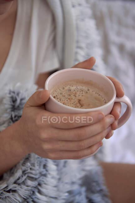 Primer plano de las manos de la mujer sosteniendo una taza de café - foto de stock