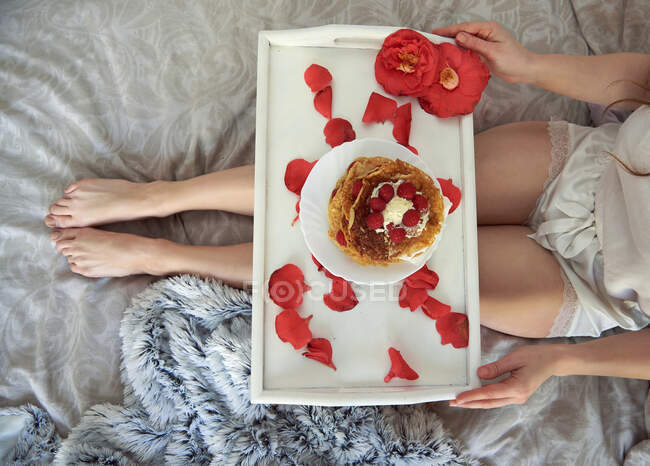 From above of crop anonymous female in lace pajamas sitting on bed and holding folding white table strewn with red rose petals with beautiful dessert decorated with whipped cream and raspberries — Stock Photo