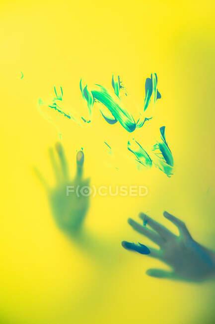 Ковзанка з розфарбованими руками стоїть позаду напівпрозорої жовтої стіни з пензлем. — стокове фото