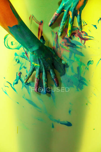 Crop craftswoman with painted hands standing behind translucent yellow wall with brushstrokes — Stock Photo